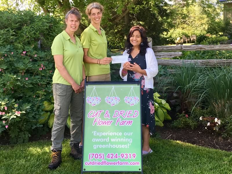 Ami Gopal, Director of Development for Water First visited the farm to collect a cheque for $900 from the farm's owner, Katie Dawson and winning designer Kelly French.
